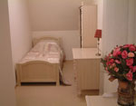 A bedroom with 2 single beds and 1 child's bed