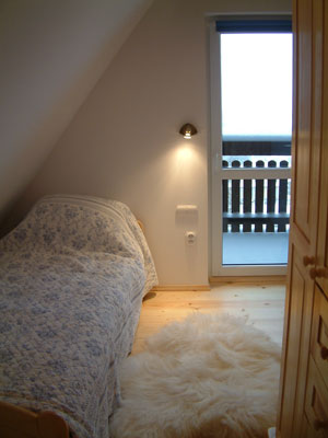 Blue bedroom with comfortable bed, sheepskin rugs and natural wood floor